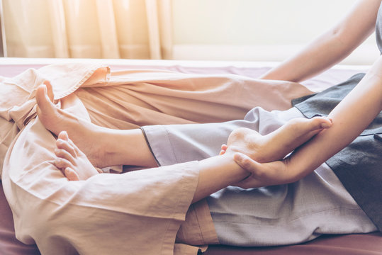 Thai massage spa with Thai traditional massage in wellness center. Relaxed Woman recipient got leg therapy relief the healing acupressure of traditional Thai massage at luxury spa wellness center.