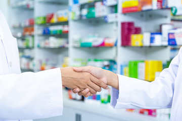 Close up picture of doctor and pharmacist shaking hands in the pharmacy.
