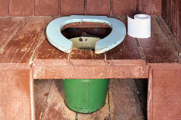 Toilet seat of a country wooden outdoor toilet with a metal bucket as a waste tank and a roll of a paper close up