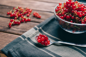 Ripe red currant on a wooden table.