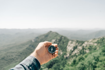 Male hand with magnetic compass high in mountains, pov.