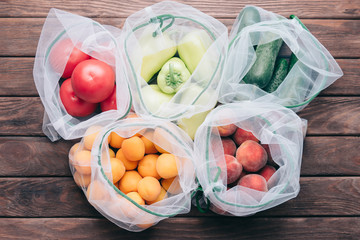 Fresh fruits and vegetables in reusable eco bags.