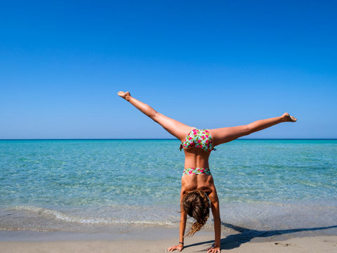 Slim and athletic girl doing a cartwheel on a wonderful beach with crystal clear water -vacation-fitness-wellness