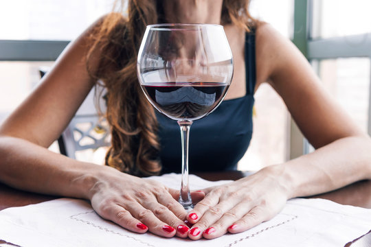 Drunk woman sitting at a table and holding a glass of wine close up. Female alcoholism.