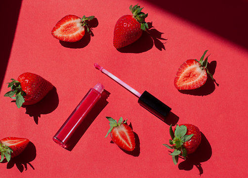 Red lip gloss beauty concept flat lay with fresh strawberries on the red background.