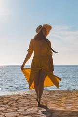woman walking in yellow sundress by stone seaside