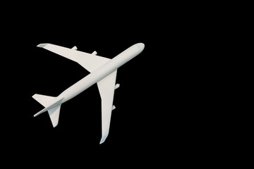 White model airplane on black background with copy space. Flat lay design. Top view.