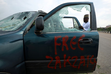 """""""Free Zakzaky"""" reads on a damaged car outside the National Assembly in Abuja"""