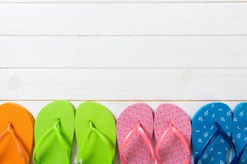 a lot of flip flop colored sandals, summer vacation on wooden background, copy space top view