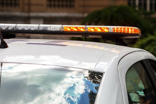 Strobe light flashes orange, mounted on a police car