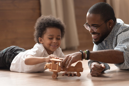 Happy african dad and child boy play with toy plane