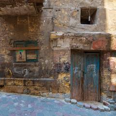 Grunge stone bricks wall with Broken wooden door and closed broken shutter window in abandoned Darb El Labana district, Cairo, Egypt