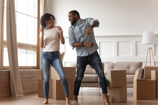 Happy african couple dancing laughing in living room with boxes
