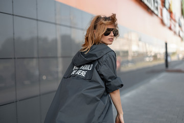 Beautiful hipster young redhead woman in trendy black sunglasses in a stylish long fashion jacket walks around the city near a gray building. Modern attractive girl goes and turns around. Wall mural