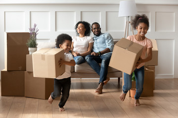 Happy little african kids holding boxes play on moving day