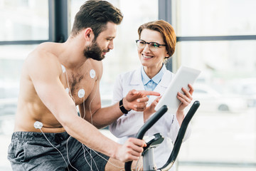 smiling doctor with digital tablet near shirtless sportsman during endurance test Wall mural