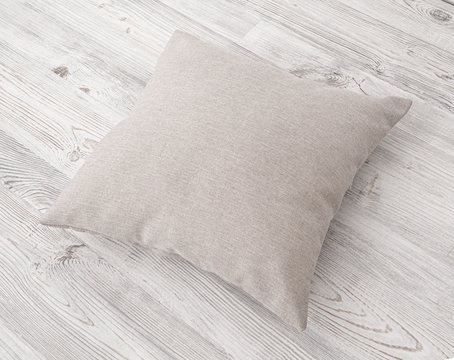 Gray cushion on the wooden table side view. Soft square pillow on a wooden surface .