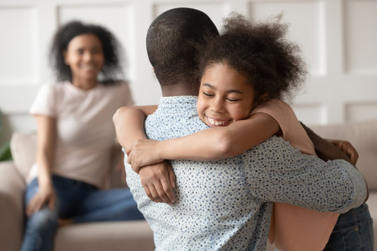 Happy little african kid daughter embracing black dad at home