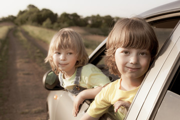 two cheerful child sitting in the car