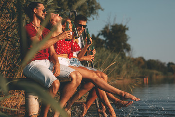 Group of young people sitting on a wooden platform by the river drinking beer and splashing their feet in water on warm summer day