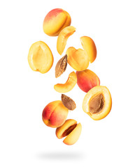 Whole and sliced fresh apricots in the air, isolated on a white background