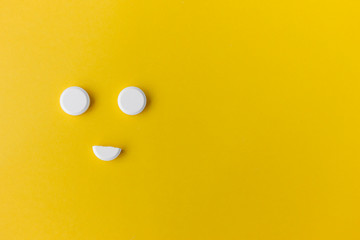 white round pills on a yellow background with copy space in the form of a smiley