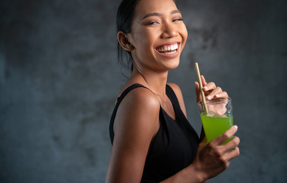 Portrait of beautiful young smiling woman in black t-shirt holding glass with healthy juice over concrete background
