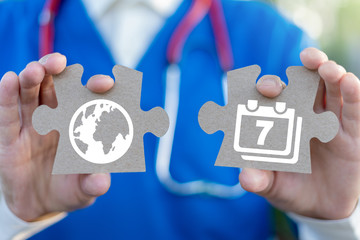 International world health day concept. Doctor or pharmacist holds two puzzle pieces with calendar 7 april and earth planet icons.