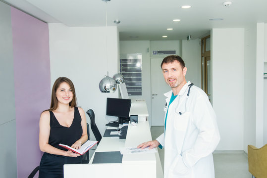 Portraits of smiling male doctor and young friendly female receptionist at hospital reception desk. Occupation, staff interaction concept. Selective focus, space for text.