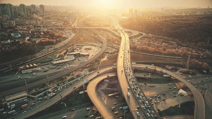 City Road System with Sight Traffic Jam Aerial View. Urban Congested Highway Lane Transport Navigation Scene. Busy Downtown Building Vehicle at Sunset. Travel Concept Drone Flight Shot