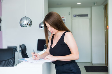 Young female manager standing at reception desk in office hall and plans working schedule, writes in notebook, makes notes of useful information, holds pen, dressed casually, writes down her thoughts