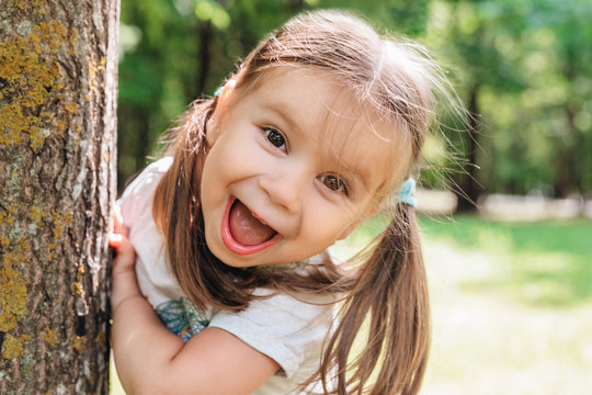 Close-up portrait of an excited little girl laughing in park