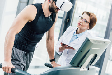 sportsman in vr headset training on treadmill near doctor during endurance test in gym