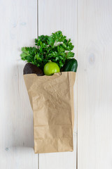 Fresh vegetables and greens in a paper bag: avocado, cucumber, lime, cilantro and dill. Platic free...