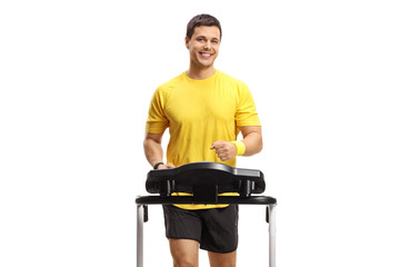 Young smiling guy running on a treadmill