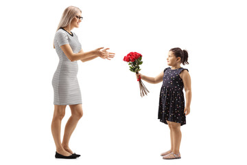Little girl giving a bunch of red roses to a young woman