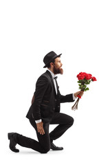 Bearded man kneeling and holding red roses