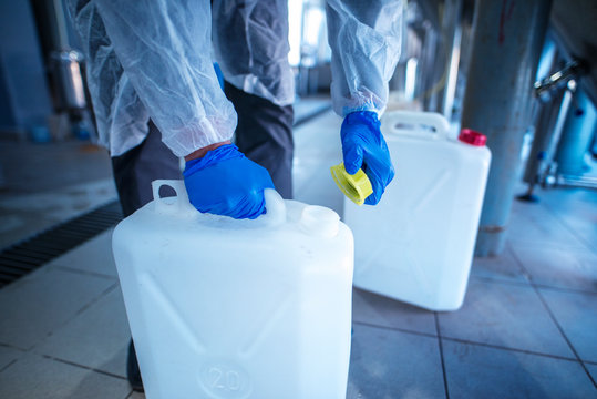Unrecognizable person technologist in white protective suit handling acid or detergent in chemical industry. Industrial worker opening plastic canister to use chemicals.