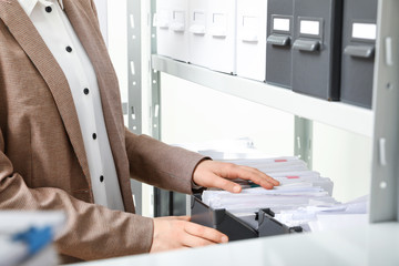 Woman taking documents from folder in archive, closeup