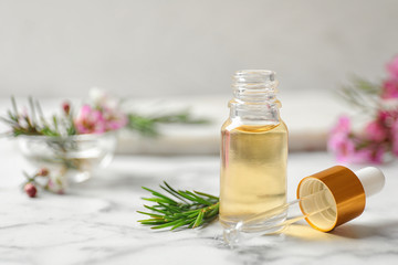 Composition with bottle of natural tea tree oil on white marble table. Space for text Fototapete