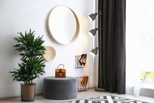 Hallway interior with big round mirror and ottoman chair near white wall