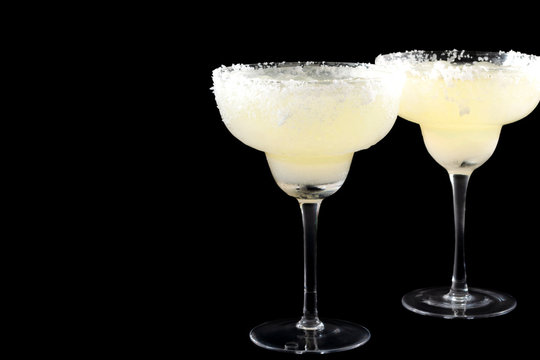Tropical cocktail, Mexican drink and cinco de mayo party concept theme with two glasses of margarita on the rocks with salted rims isolated on black background with copy space