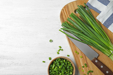 Flat lay composition with fresh green onions on white wooden background. Space for text