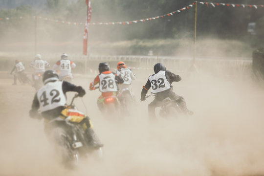 Racing motorcycles making a lot of dust when accelerating after the turn on the dirt racing track.