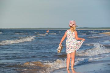 dziewczynka w letniej sukience na morskiej plaży,