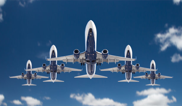 Bottom View of Five Passenger Airplanes Flying In Formation In The Blue Sky