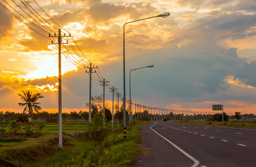 Landscape in the fields and background, orange sky, twilight and electric poles on the road