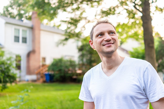 Young man happy smiling homeowner in Herndon, Northern Virginia, Fairfax county residential neighborhood in spring or summer by house backyard