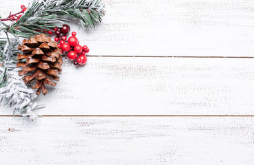 Christmas decorations on a white wood background with copy space. Pine cones, garland, berries and pine branches