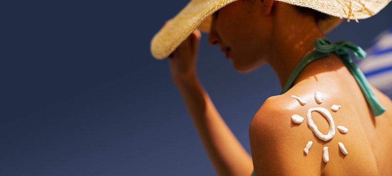 Woman tanning at the beach with sunscreen cream